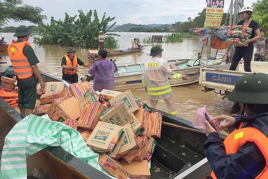 Rescuers load boats with boxes of food, mostly instant noodles, that will be distributed to local residents in Thach Thanh district, in the central province of Thanh Hoa, yesterday. Northern Hoa Binh is the hardest-hit region, with 11 dead and 21 mis