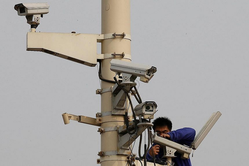 "A man working on a security camera in Tiananmen Square. China's anti-corruption campaign to ""kill tigers and swat flies"" - or to go after both senior officials and the rank and file - seems set to continue."