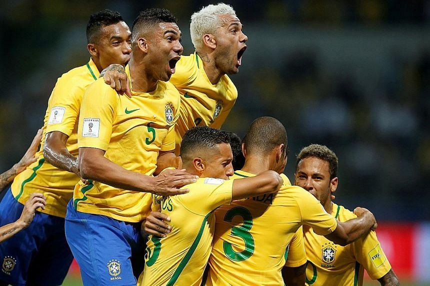 Brazil's players celebrating their first goal in the 3-0 win over Chile in Sao Paulo on Tuesday, a result that enabled them to top the South American qualifying group and which knocked the visitors out. The Selecao have won 10 and drawn two of their