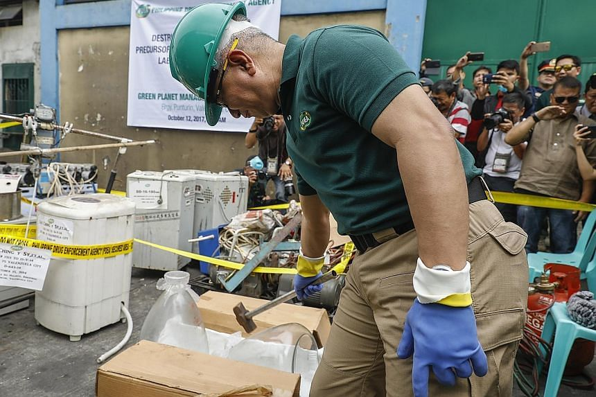 """Philippine Drug Enforcement Agency director-general Aaron Aquino destroying seized equipment used to manufacture illegal drugs in Valenzuela City, north of Manila, yesterday. Presidential spokesman Ernesto Abella said that """"higher echelons of the syn"""