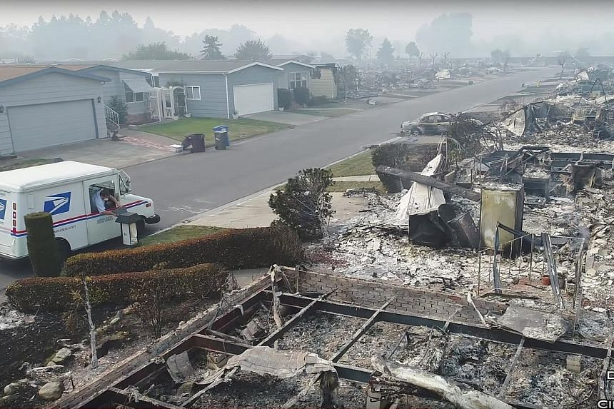 A postman delivering mail on Tuesday in fire-devastated Santa Rosa, California, in a screengrab from a video on social media. Helicopters rescued 42 people in the town of Napa from the fires.