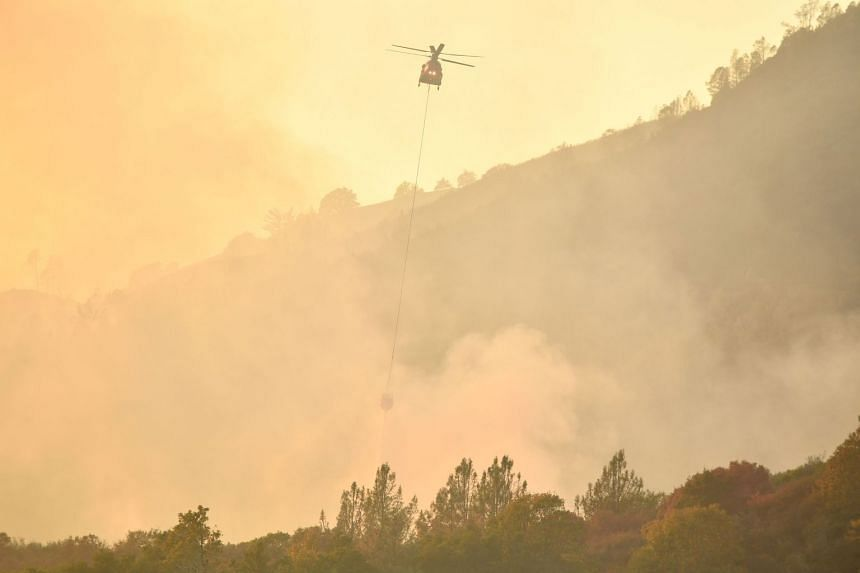 A helicopter drops water on flames in Calistoga, California on Oct 11, 2017.
