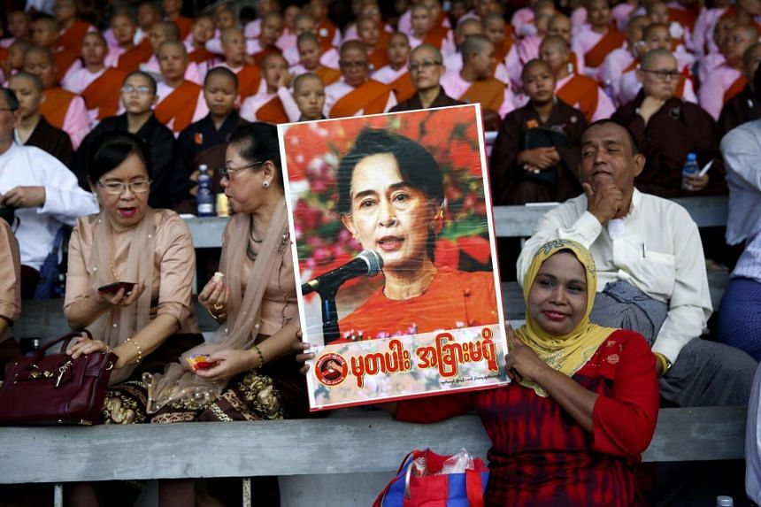A Muslim woman holds the image of Myanmar State Counsellor Aung San Suu Kyi as she attends Interreligious Gathering of Prayer for Peace ceremony in Yangon, Myanmar on Oct 10, 2017.