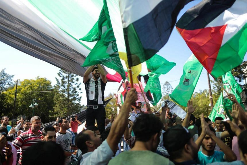 Palestinians wave the flags of Egypt, Palestine, Fatah and Hamas as they gather in Gaza City to celebrate on Oct 12, 2017.