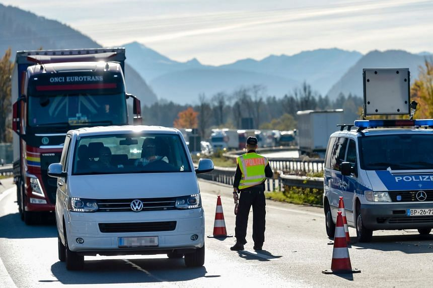 A German police officer monitors cars and trucks queuing to cross a border control between Austria and Germany.