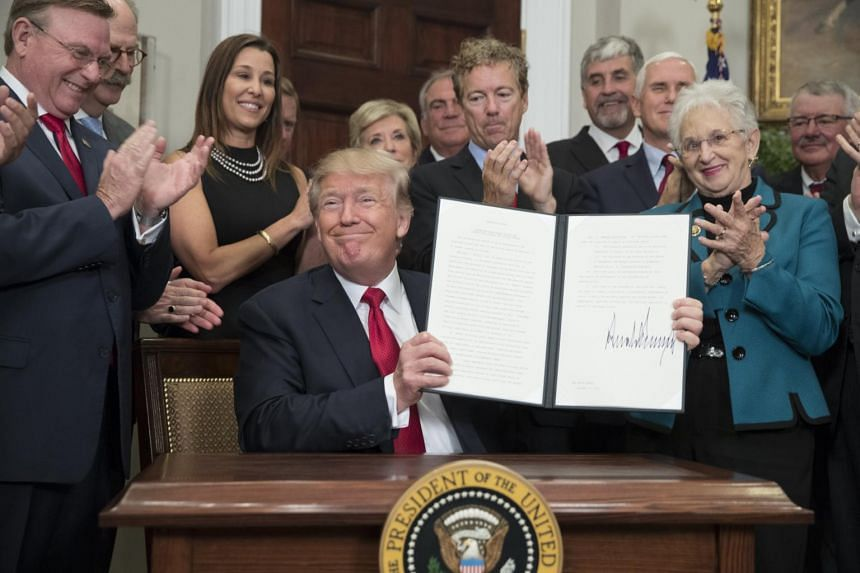 US President Donald Trump (centre) holds up an executive order on healthcare after signing it during a ceremony in the Roosevelt Room of the White House in Washington, DC, USA, on Oct 12, 2017.