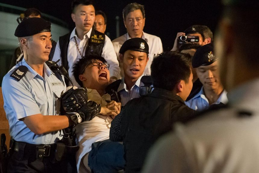 Police officers arresting Joshua Wong after he climbed onto the Golden Bauhinia statue during a protest in Golden Bauhinia Square in Hong Kong.