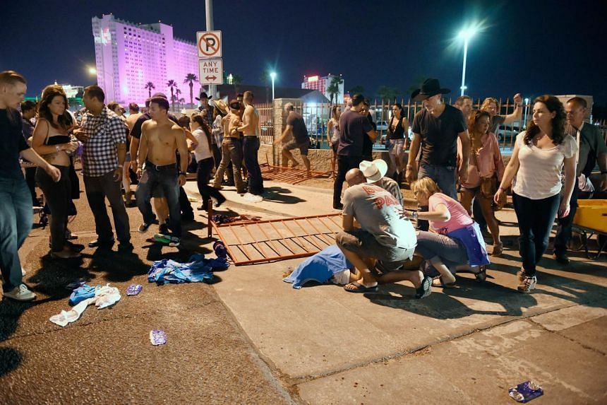 People tend to the wounded outside the festival ground near the Mandalay Bay hotel.