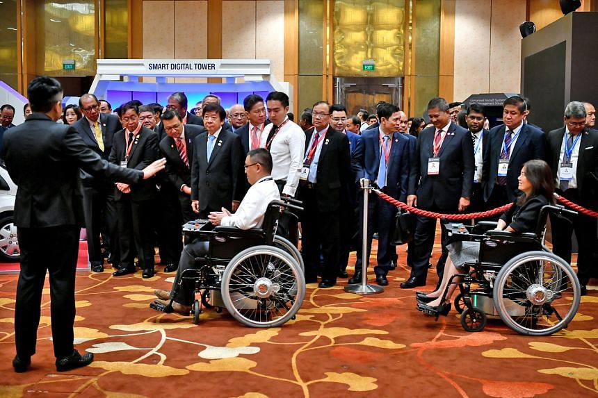 Coordinating Minister for Infrastructure and Transport Minister Khaw Boon Wan and Asean transport ministers checking out the Smart Wheelchair System, which uses visual markers for the wheelchairs to move in a convoy autonomously, at the Future of Tra