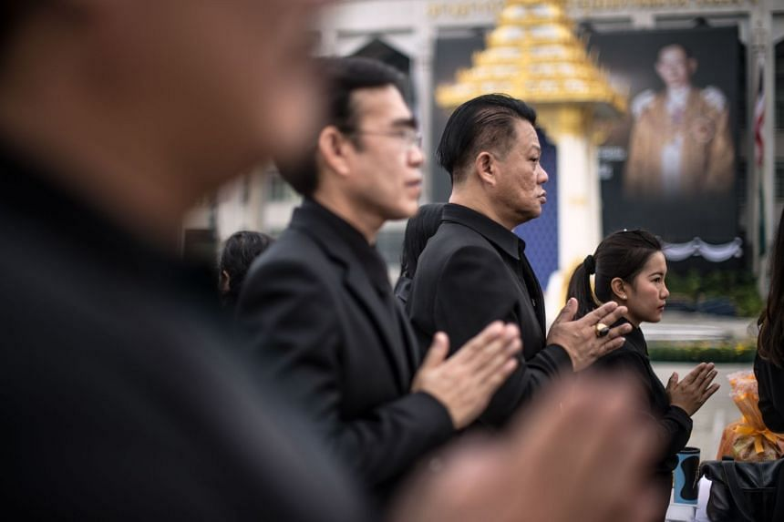 People praying during a ceremony led by monks in front of Bangkok's City Hall on Oct 13, 2017, marking one year since the death of King Bhumibol Adulyadej.