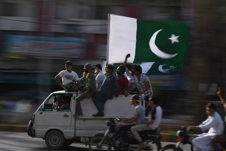 Pakistani residents carry a national flag for Independence Day in Karachi.