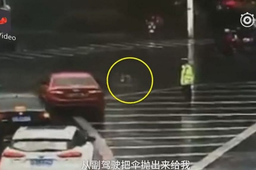 The driver tossed an umbrella out of the front window of the car as it moved off from the junction.