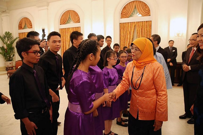 President Halimah Yacob meeting members of the MINDS Lee Kong Chian Gardens School choir before their performance at the Community Chest Awards ceremony at the Istana yesterday. She is the patron-in-chief of the National Council of Social Service, wh