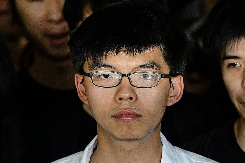 Pro-democracy activists gathering during a protest outside the High Court in Hong Kong yesterday. Supporters sang jailed pro-democracy leader Joshua Wong (above) a birthday song in the courtroom to mark his 21st birthday.