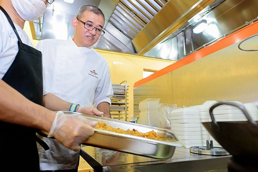 An inmate operating an oven in the new kitchen. Food prepared by the inmates, ensuring nursing home residents get nutritious meals. One of the many state-of-the-art machines used in the cooking process. This machine can cook rice and noodles, and ser