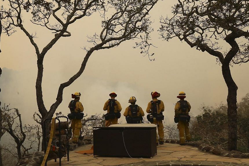 Firefighters in Sonoma County, California, facing a wall of smoke rising from the Norrbom fire burning across a valley on Wednesday. The county accounted for 17 of the North Bay fatalities, all from the Tubbs fire, which now ranks as California's dea
