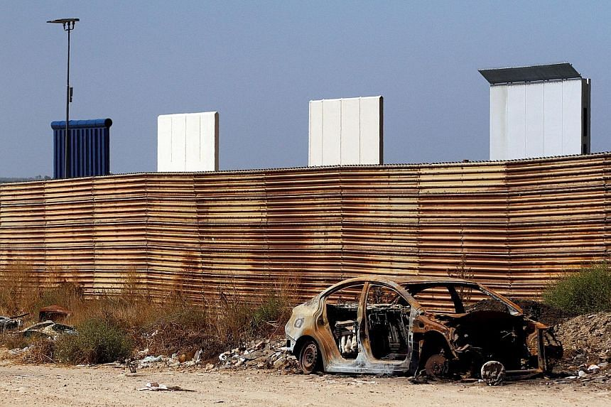 Prototypes for the United States' border wall with Mexico seen behind the current fence in Tijuana, Mexico, on Thursday.