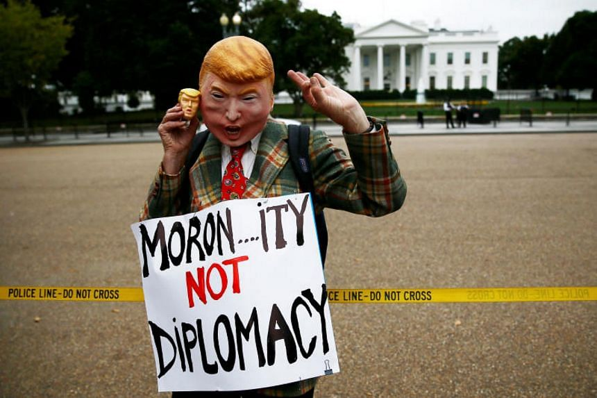 A lone protester outside the White House wears a Donald Trump mask in opposition to President Trump's announcement about the Iran nuclear deal and his policy towards Iran at the White House on Oct 13, 2017.