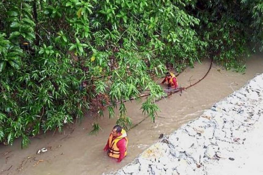 The search: Firemen looking for the victims at Lubuk Semilang in Kuah, Langkawi.