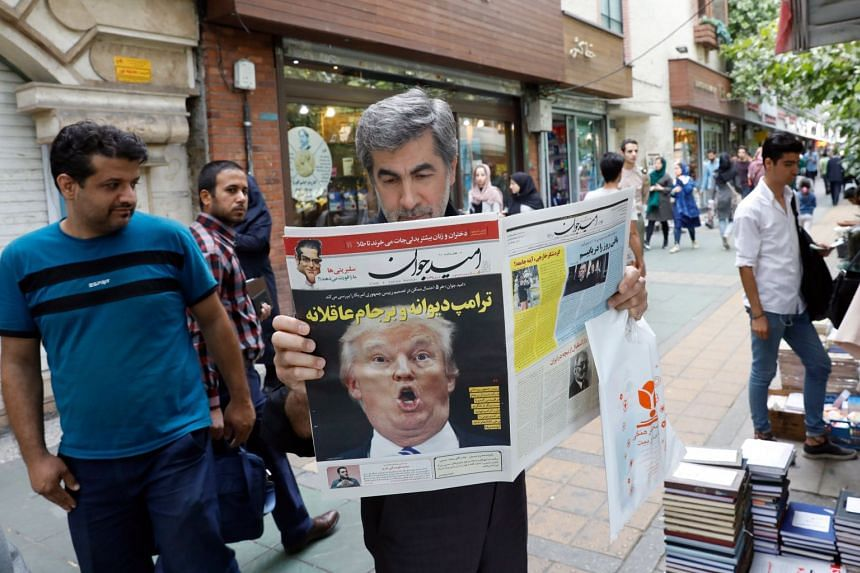 A man reads a copy of Iranian daily newspaper Arman, with a picture of US President Donald Trump on its front page.