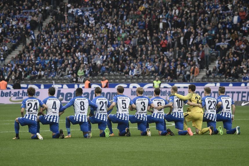 Berlin's players kneel down before the match against Schalke.