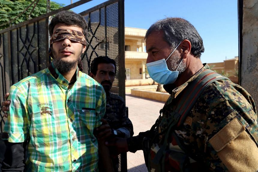 SDF members escort a blindfolded civilian detainee suspected to be an ISIS militant in Raqqa, Oct 12, 2017.