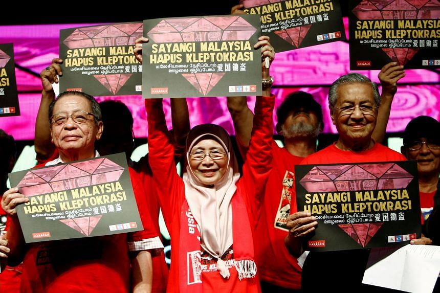 """Former Malaysian PM Mahathir Mohamad (right), opposition leaders Wan Azizah (centre) and Lim Kit Siang hold placards reading """"Love Malaysia, End Kleptocracy""""."""