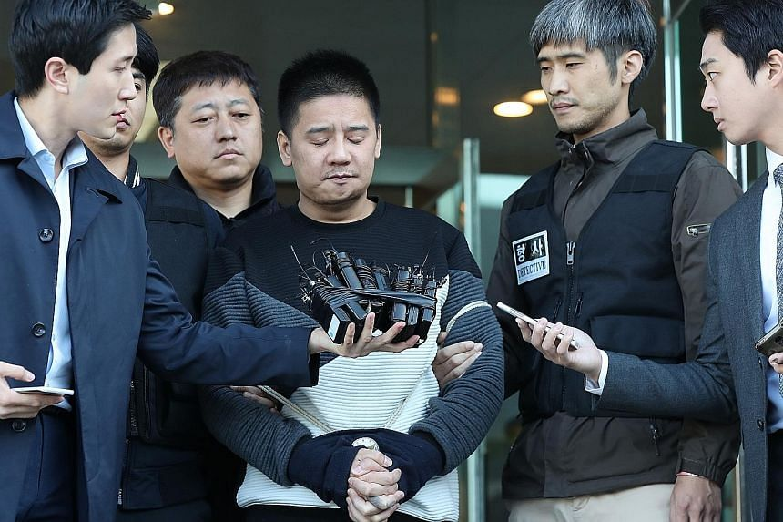 Murder suspect Lee Young Hak facing questions from reporters at the Chungang Police Station in Seoul last Friday.