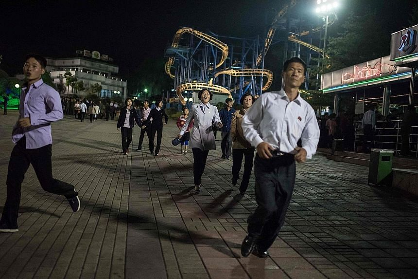 North Koreans at a fun fair in Pyongyang last month. On a recent trip to North Korea, the writer found the country to be galvanising its people to expect a nuclear war with the US. High school students march in the streets in military uniform daily t