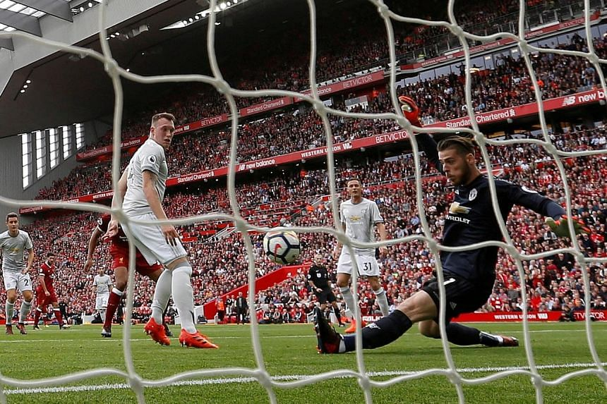 Manchester United's Phil Jones (left) watches as his goalkeeper David de Gea makes a wonder save against Liverpool's Joel Matip. It was the highlight of the match.
