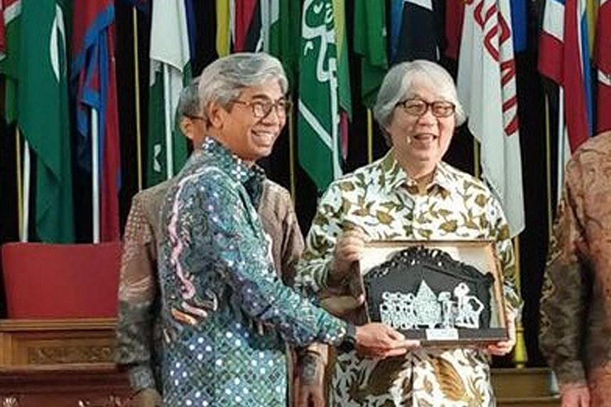 Professor Tommy Koh receiving the award from Indonesia's Deputy Foreign Minister H. Abdurrahman Mohammad Fachir, in Bandung, West Java yesterday.