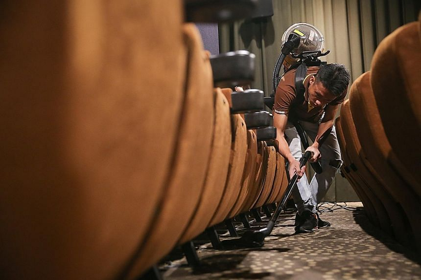 Armed with a heavy-duty vacuum cleaner, Mr Lee Trung Cuong from Jusclean Services, Golden Village Paya Lebar's cleaning contractor, cleaning up a cinema hall after its last show last Wednesday. It takes about an hour to clean up each hall after the l