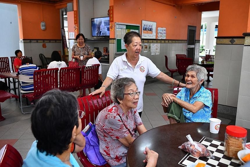 Madam Heng (standing, in white), 69, a cafe corner staff member, chatting with residents Chong Siew Heng (middle), 81, and Lim Bong Chee (right), 80, at a cafe corner at Block 291B, Compassvale Street, on Friday. The cafe corner, an initiative starte