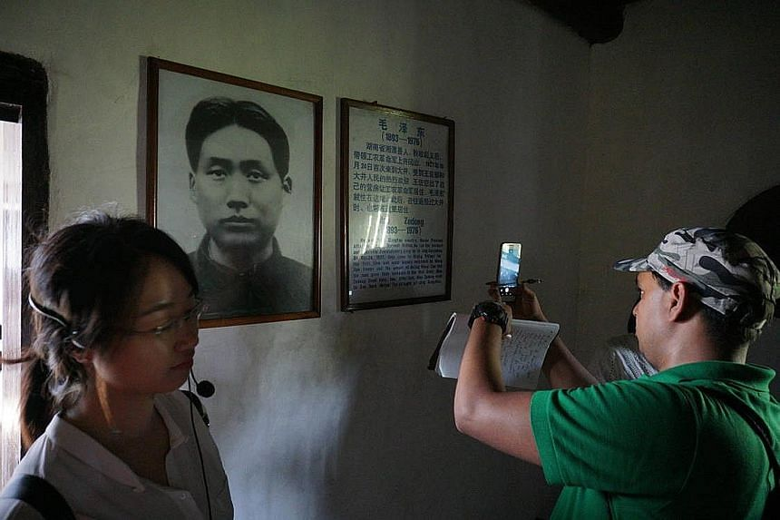 """""""Red Army"""" biscuits and souvenirs are widely available at shops in Jinggangshan. Visitors to Ciping taking pictures in the room that Mao Zedong stayed in during the early part of the Chinese Revolution. The former Red Army base is now a key tourism s"""
