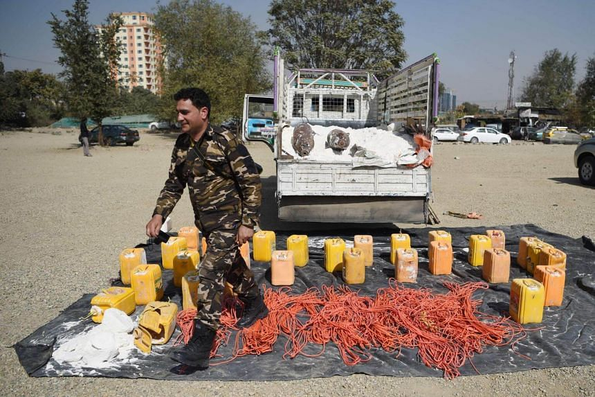 An Afghan security force personnel walks next to containers filled with explosive material after presenting to the media at the National Directorate of Security (NDS) headquarters in Kabul on Oct 15, 2017.