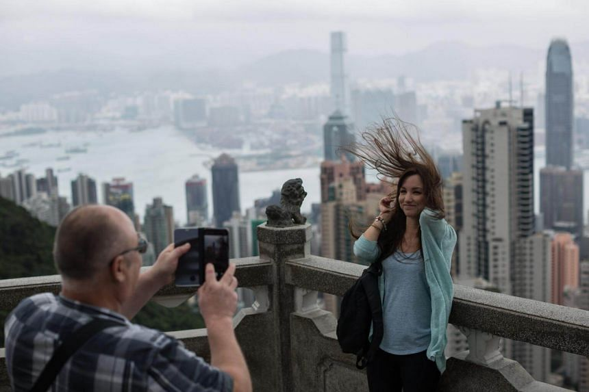 Tourists take photographs from a panoramic lookout on Victoria Peak during windy weather brought by typhoon Khanun in Hong Kong, China on Oct 15, 2017.