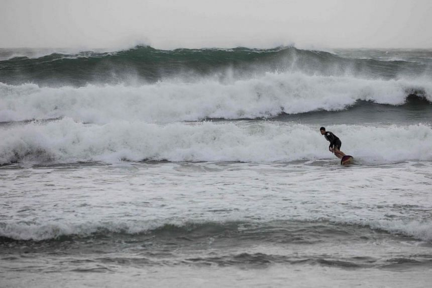 A surfer rides a wave at a beach in Hong Kong on Oct 15, 2017 as Typhoon Khanun moved across the northern part of the South China sea.