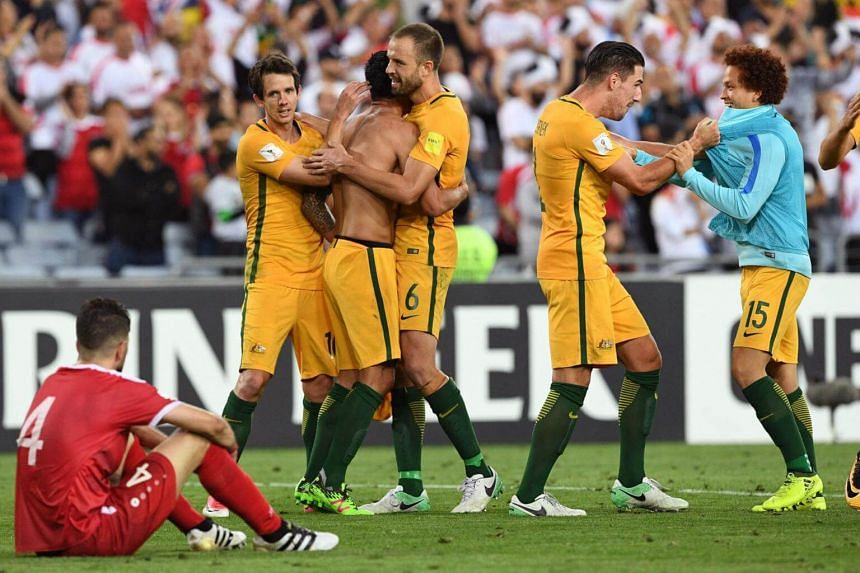 Australian players celebrate after they defeated Syria in their 2018 World Cup football qualifying match played in Sydney on Oct 10, 2017.