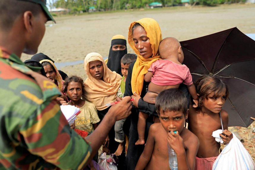 A Bangladeshi army soldier hands over a relief card to Rohingya refugees, who fled from Myanmar a day before as they walk to a relief centre in Teknaf, near Cox's Bazar in Bangladesh, on Oct 13, 2017.