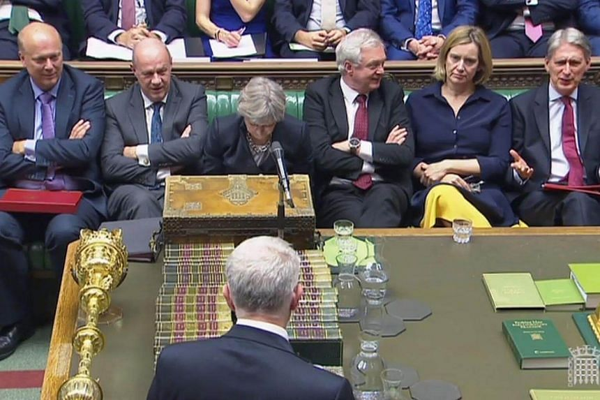 Britain's Prime Minister Theresa May (centre) as she listens to Britain's opposition Labour party's leader Jeremy Corbyn (bottom) address MPs in the House of Commons in London on Oct 9, 2017.