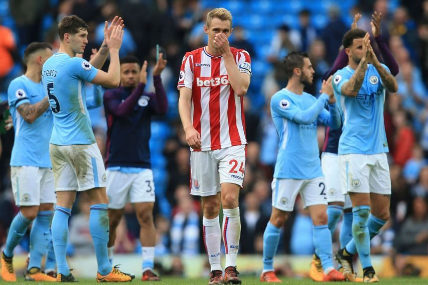Stoke City's Scottish midfielder Darren Fletcher reacts as Manchester City players celebrate their victory.
