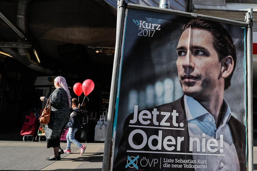 A woman with a child holding red balloons passes an election poster reading 'Now. Or never!' of Austrian Foreign Minister Sebastian Kurz, the leader and top candidate of the Austrian Peoples Party (OeVP) in Vienna.