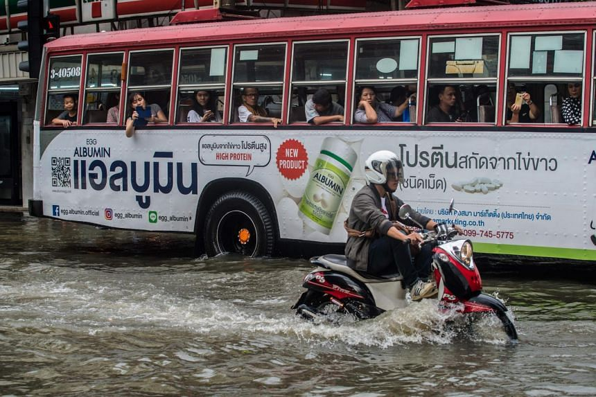 A man drives his motorcycle on a flooded street in Bangkok on Oct 14, 2017.