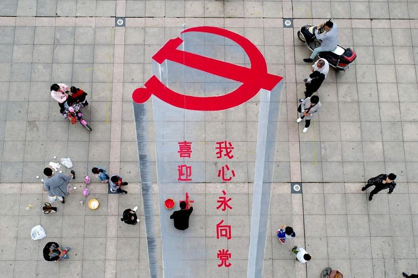 A man working on a 3D street painting of the emblem of Chinese Communist Party to celebrate the upcoming Party Congress.
