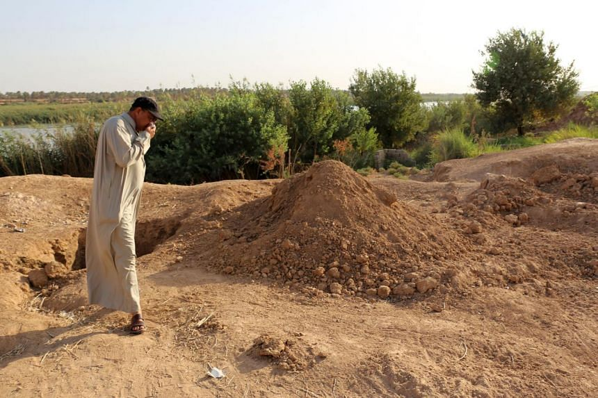 An Iraqi man inspects the site of a pit containing the bodies of ISIS fighters in the Iraqi town of Dhuluiyah.