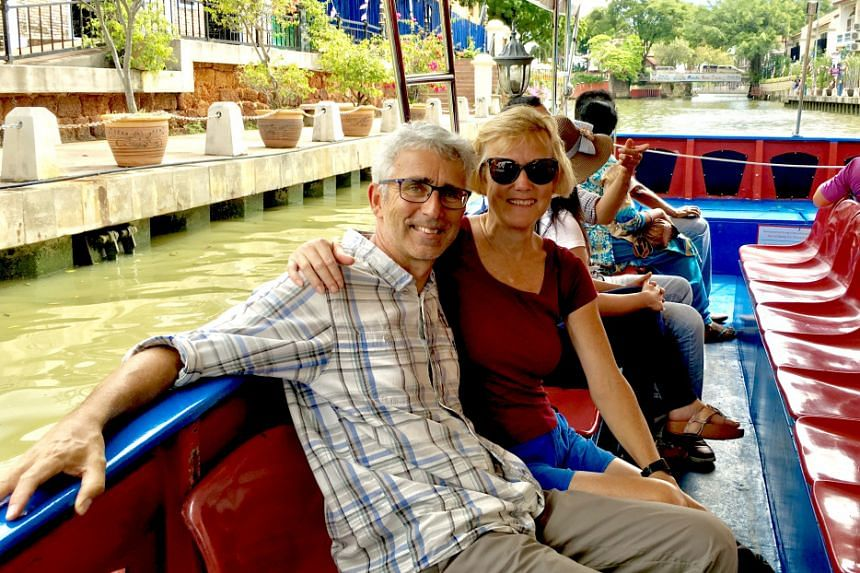 The couple in a photo from their blog, taking a boat ride in Malacca, Malaysia.