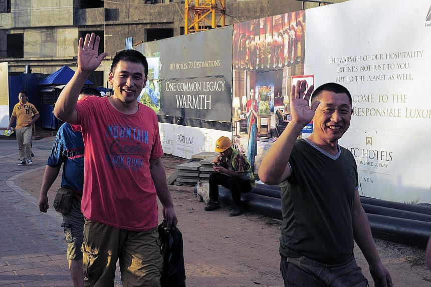 Chinese construction workers outside the Shangri-La hotel and apartment complex that is due for completion this year.