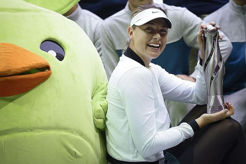 Maria Sharapova showing off her Tianjin Open trophy yesterday. It was the Russian's 36th tour title.