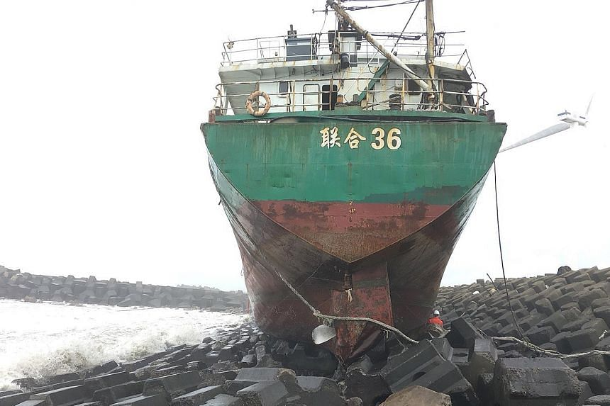 A Mongolian freighter run aground on the coast of Changhwa county, western Taiwan, due to Typhoon Khanun last Saturday. Tourists making the best of the wild weather yesterday at The Peak in Hong Kong, where the weather warning went down to the second