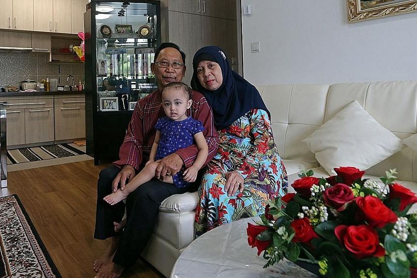 Mr Ahmad Mohammad Said, 66, with his wife Madam Norhati Nordin, 63, and their granddaughter Nurul Ilya Janah, 18 months, in their new studio flat. Above: Mr Heng Gee Choo, 64, and his wife Sie Gik Moi, 59, with their grandchildren Aden Cai, five, and